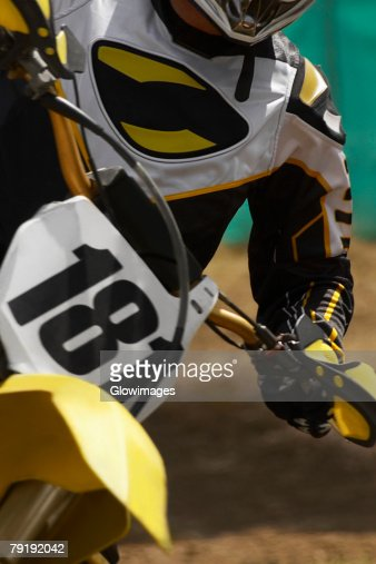 Mid section view of a motocross rider riding a motorcycle : Stock Photo