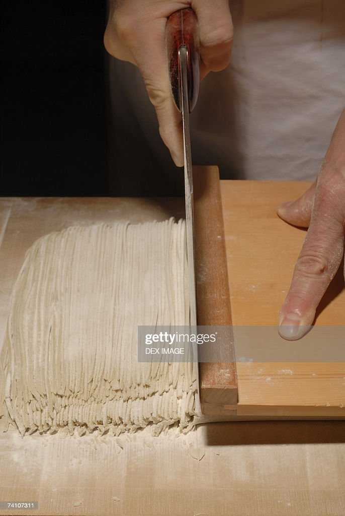 Mid Section View Of A Person Cutting Noodles Stock Photo ...