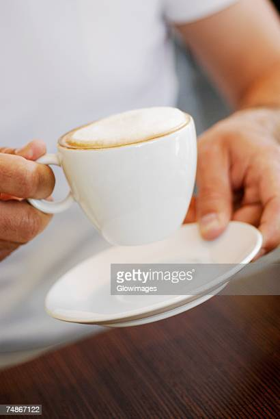 Mid section view of a person holding a coffee cup