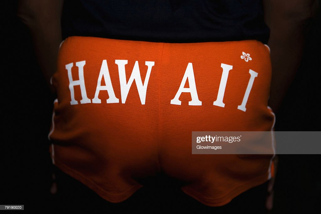 Mid section view of a person wearing shorts with Hawaii printed on it : Stock Photo