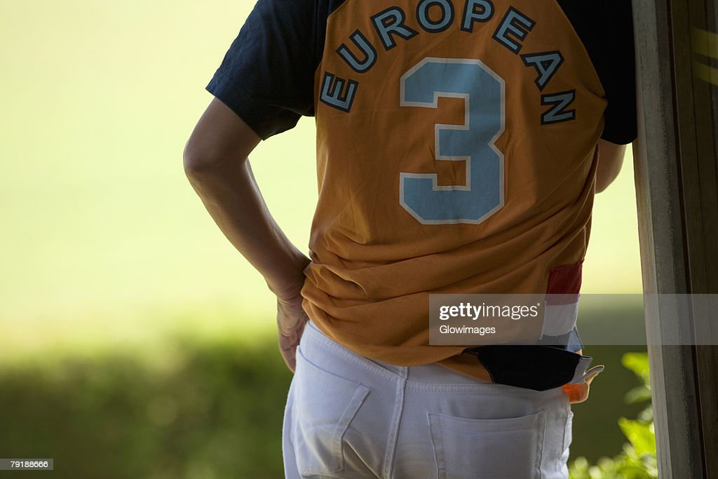 Mid section view of a player standing with his hand in his pocket : Stock Photo