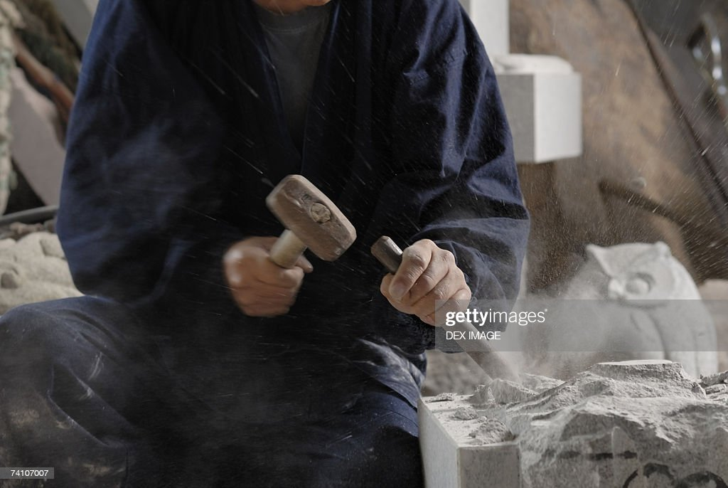 Mid section view of a sculptor carving stone with a chisel and a hammer