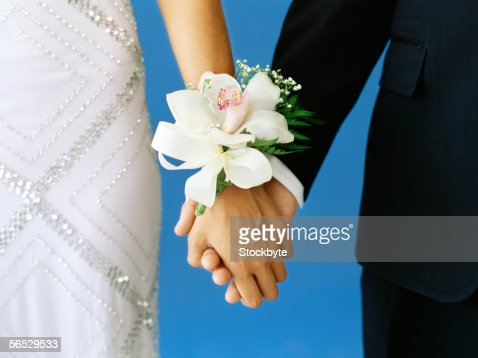 mid section view of a teenage couple holding hands
