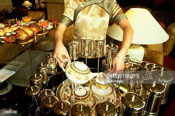 Mid section view of a waitress pouring tea in tea cups, Pudong Shangri-La, Shanghai, China