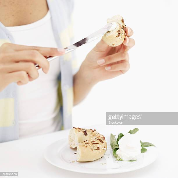 mid section view of a woman applying butter on a bagel