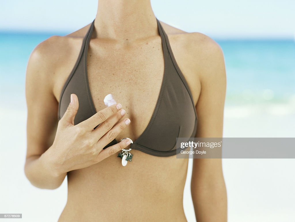 Mid section view of a woman applying moisturizer to her body
