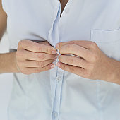 mid section view of a woman buttoning her shirt