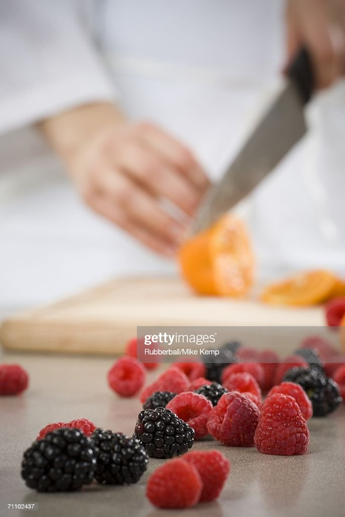 Mid section view of a woman cutting an orange : Stock Photo