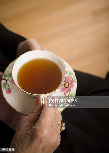 Mid section view of a woman holding a cup of tea
