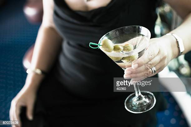 Mid section view of a woman holding a glass of cocktail