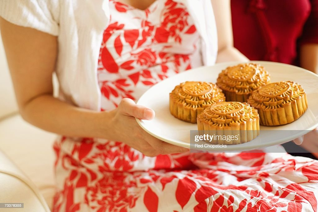 Mid section view of a woman holding a plate of cake : Stock Photo