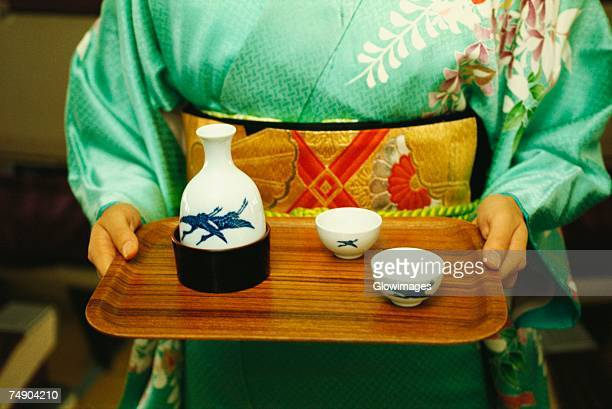 Mid section view of a woman holding saki on tray, Japan