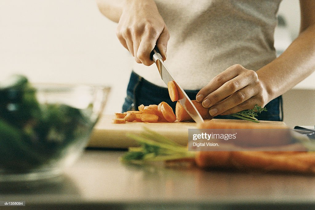 Mid Section View of a Young Woman Cutting a Carrot on a Chopping Board at a Kitchen Counter : Stock Photo