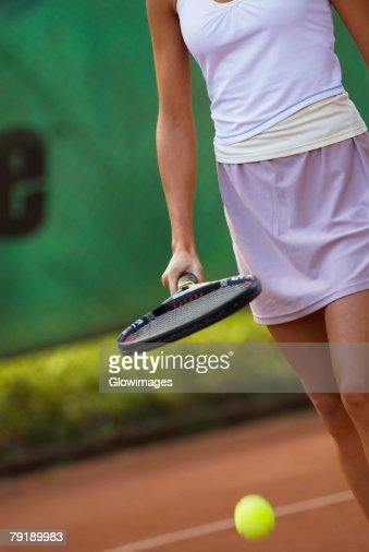 Mid section view of a young woman hitting a tennis ball with a tennis racket : Stock Photo