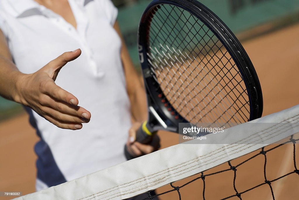 Mid section view of a young woman holding a tennis racket and reaching out for a handshake : Foto de stock