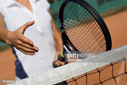 Mid section view of a young woman holding a tennis racket and reaching out for a handshake : Stock Photo