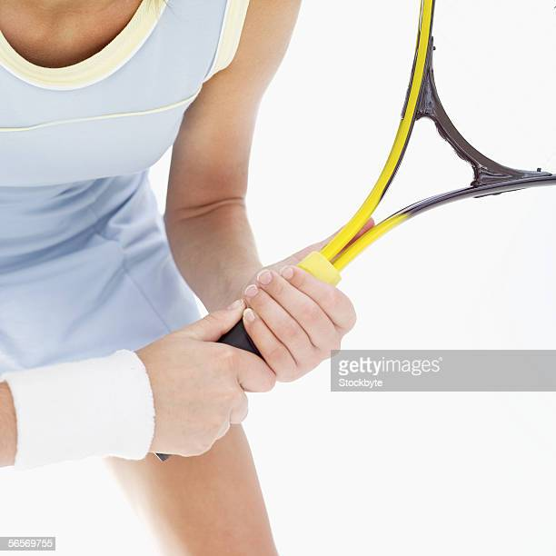 mid section view of a young woman holding a tennis racket