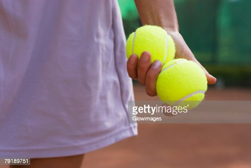 Mid section view of a young woman holding two tennis balls in her hand : Stock Photo