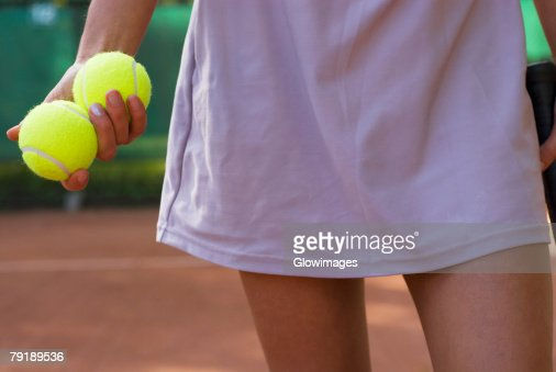 Mid section view of a young woman holding two tennis balls : Foto de stock