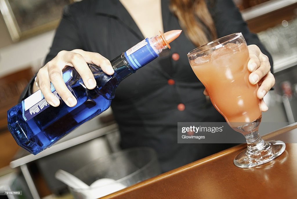 Mid section view of a young woman making a cocktail : Stock Photo