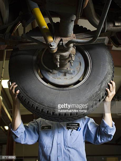 Mid section view of an auto mechanic fixing a car tire
