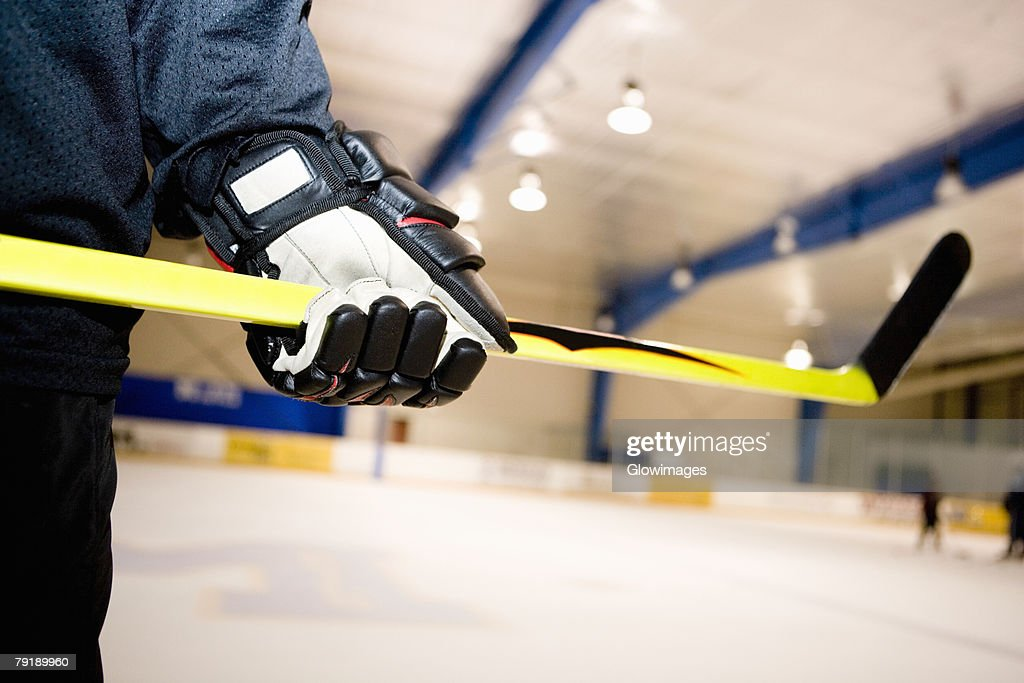 Mid section view of an ice hockey player holding an ice hockey stick : Stock Photo