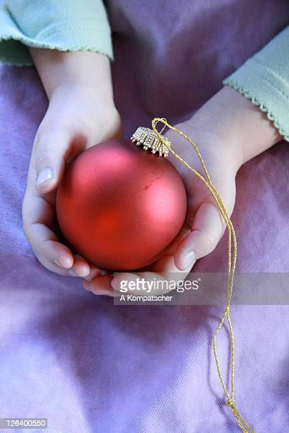 Mid section view of girl holding Christmas bauble