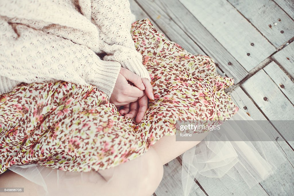 Mid section view of girl sitting on wooden floor outdoors and wearing skirt and sweater