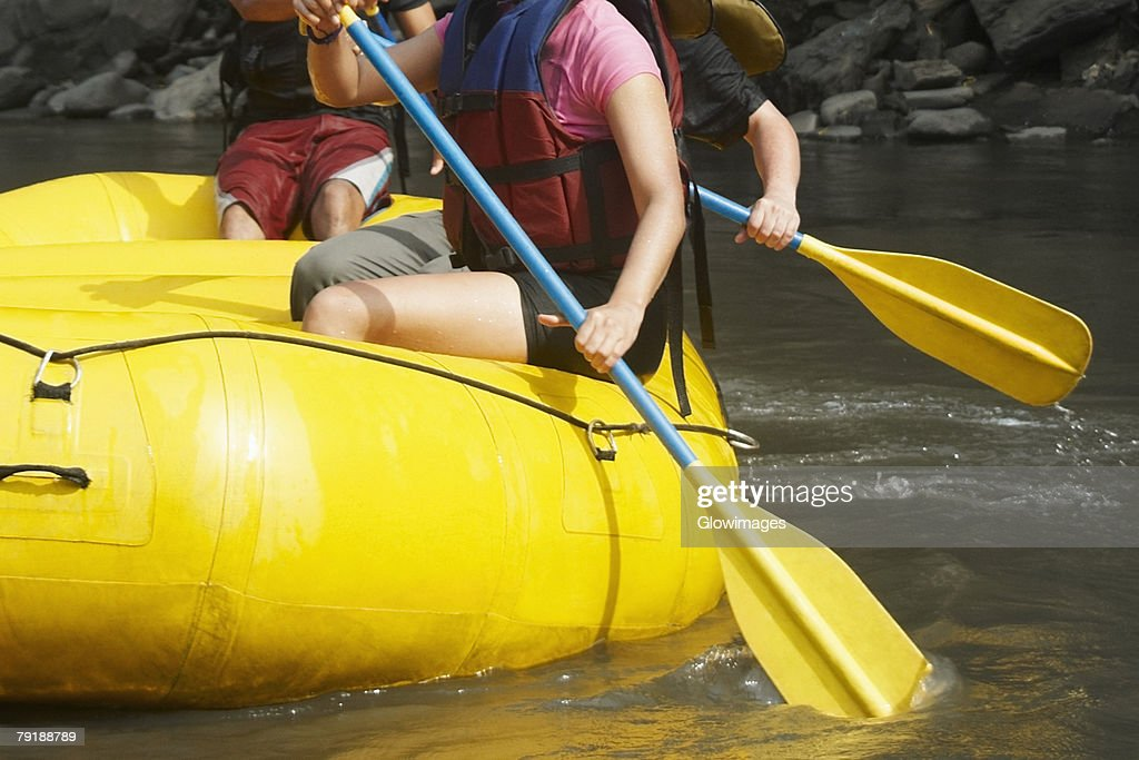 Mid section view of three people rafting in a river : Foto de stock