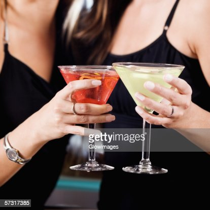 Mid Section View Of Two Young Women Toasting Martinis ...