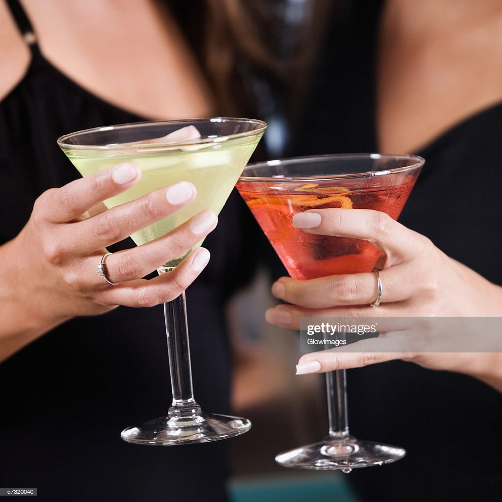 Mid section view of two young women toasting martinis