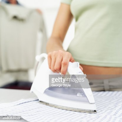 mid section view of woman ironing a shirt : Stock Photo