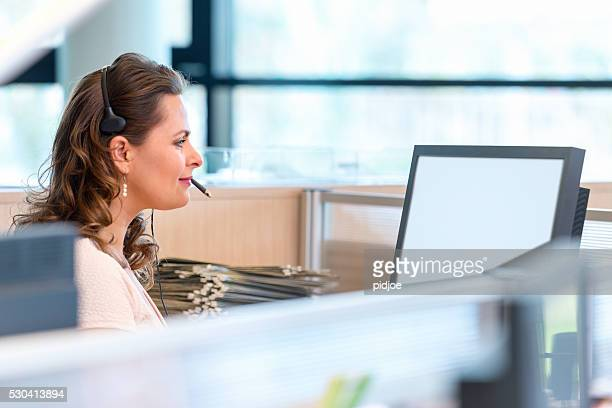 Mid thirties female professional in cubicle with headset