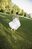 Mid-adult bride running in park