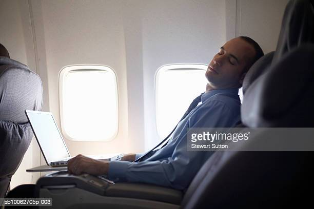 Mid-adult business man sleeping on airplane with laptop on lap