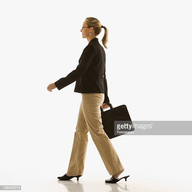 Mid-adult Caucasian businesswoman walking and carrying briefcase.