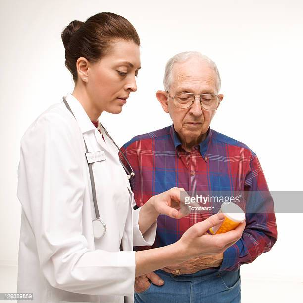 Mid-adult Caucasian female doctor pointing at prescription bottle as elderly Caucasian male looks at bottle.