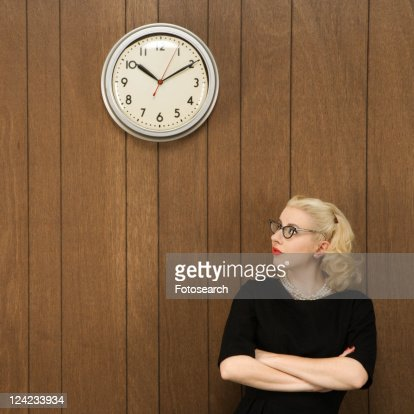 Mid-adult Caucasian female in vintage outfit looking up at clock.