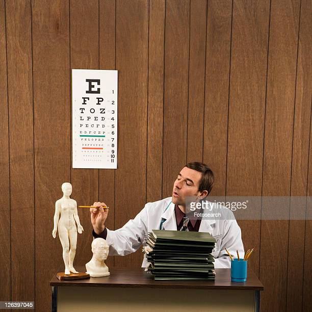 Mid-adult Caucasian male doctor sitting at desk pointing to figurine.