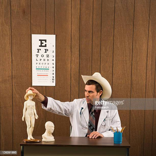 Mid-adult Caucasian male doctor wearing cowboy hat sitting at desk playing with figurine.