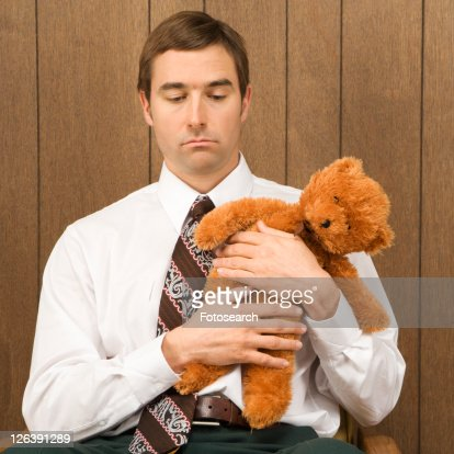 Mid-adult Caucasian male holding a stuffed animal looking sad.