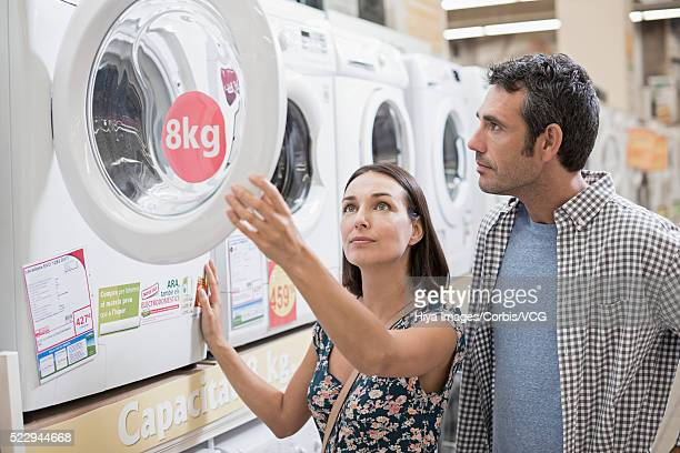 Mid-adult couple choosing washing machine in store