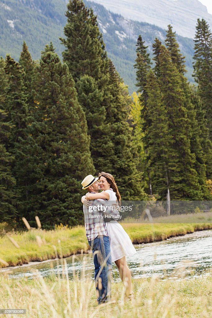 Mid-adult couple embracing and kissing at lakeshore : Stock Photo