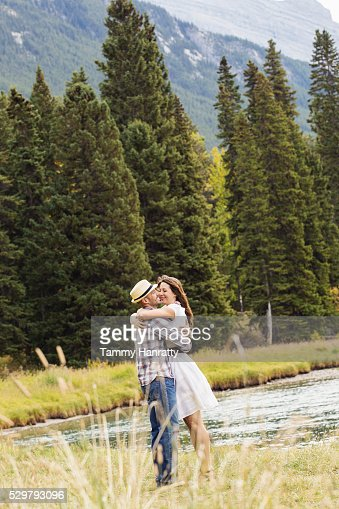 Mid-adult couple embracing and kissing at lakeshore : Stock-Foto