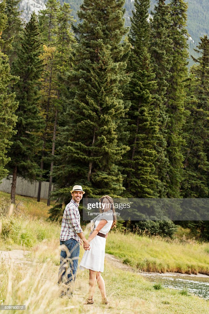 Mid-adult couple holding hands and relaxing at lakeshore : Stock Photo