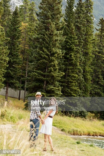 Mid-adult couple holding hands and relaxing at lakeshore : Stock-Foto