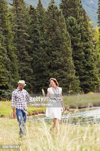 Mid-adult couple holding hands and relaxing while walking at lakeshore : Stockfoto