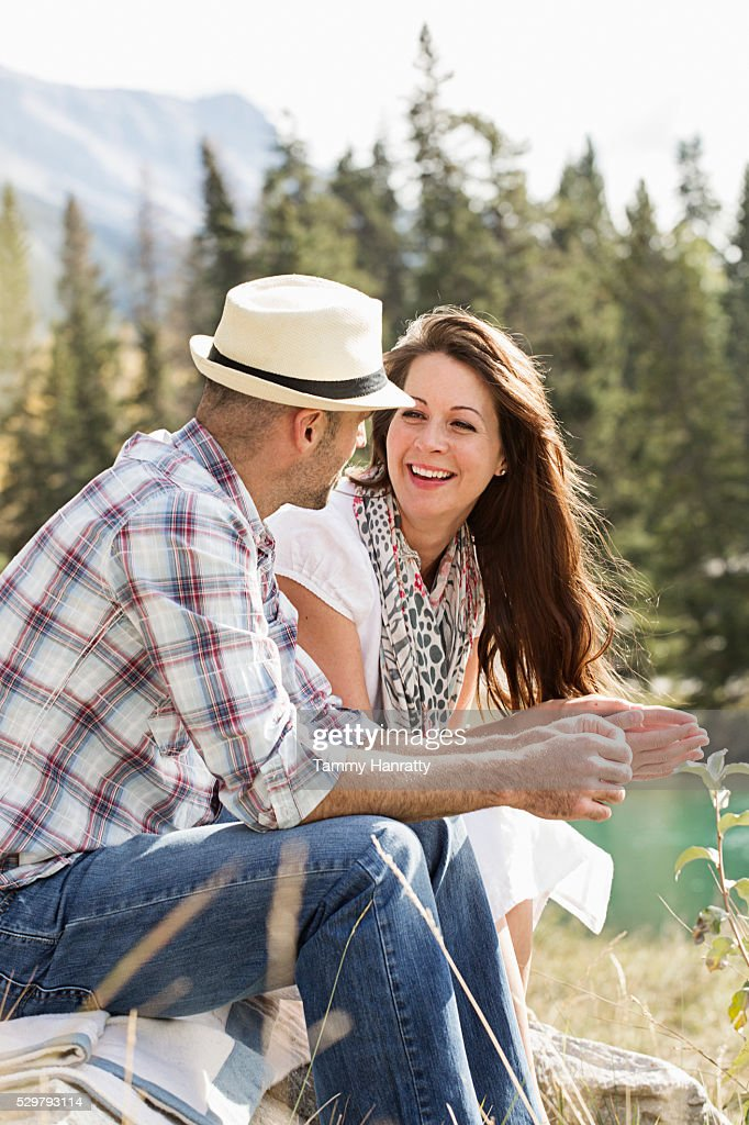 Mid-adult couple relaxing at lakeshore : Stockfoto