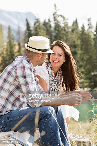 Mid-adult couple relaxing at lakeshore : Stock Photo