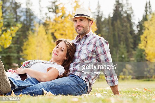 Mid-adult couple relaxing on grass : Bildbanksbilder